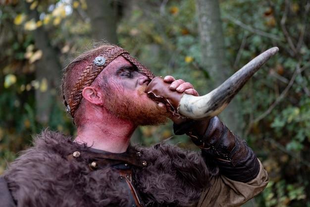 Véritable viking véritable viking buvant dans une corne à la campagne. Photo Premium