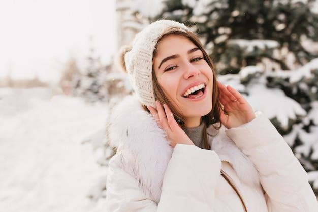 Véritables émotions Lumineuses De La Femme D'hiver En Bonnet Tricoté Souriant Sur La Rue Pleine De Neige. Photo gratuit