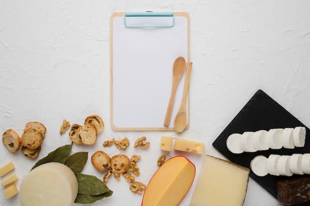 Vérité du fromage; tranche de pain; noyer; feuilles de laurier avec presse-papiers vide Photo gratuit