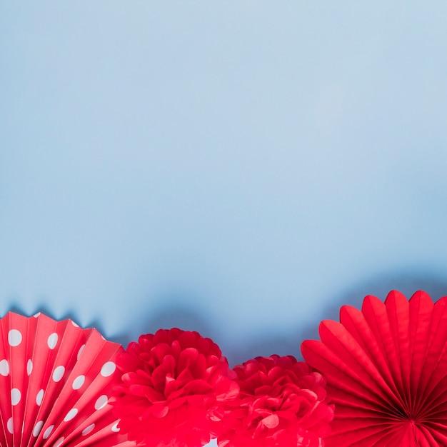 Verity de fausses fleurs d'origami rouges sur la surface bleue Photo gratuit