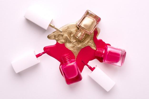 Vernis à ongles cosmétique rose et or sur blanc Photo Premium