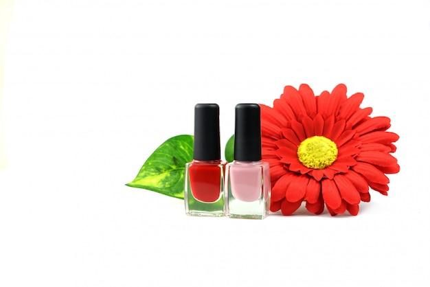 Vernis à Ongles Cosmétique Rouge Et Rose Avec Des Fleurs Sur Fond Blanc Photo Premium