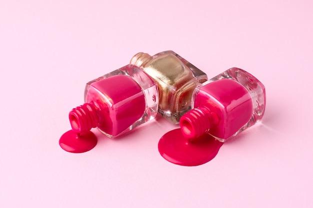 Vernis à ongles cosmétiques rose et or sur rose Photo Premium