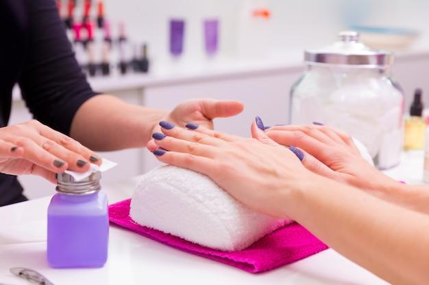 Vernis à ongles femme salon saloon enlever avec un tissu Photo Premium