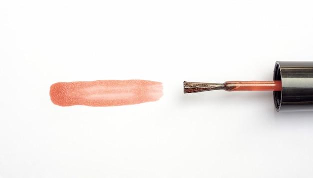 Vernis à ongles marron sur fond blanc. Photo Premium