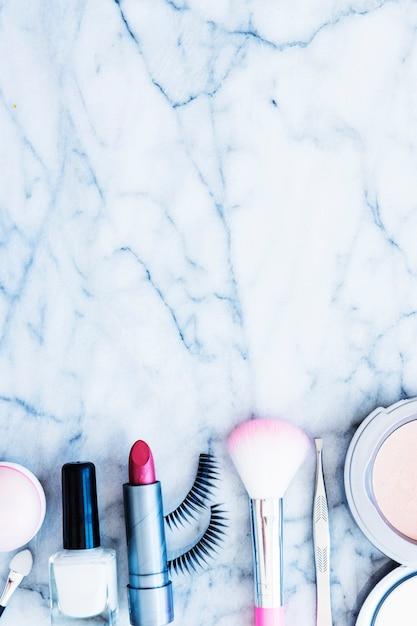 Vernis à ongles; rougit; rouge à lèvres; pince à épiler; poudre compacte et cils disposés sur un fond de marbre texturé Photo gratuit