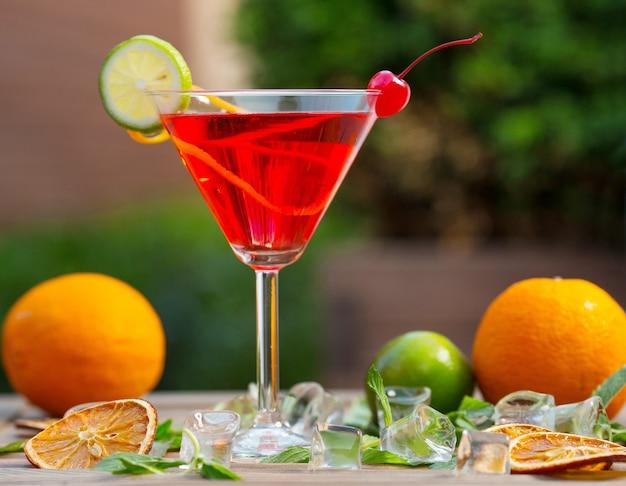 Un Verre D'alcool Rouge Cocktail Avec Une Tranche De Citron Vert Et Cerise Photo gratuit