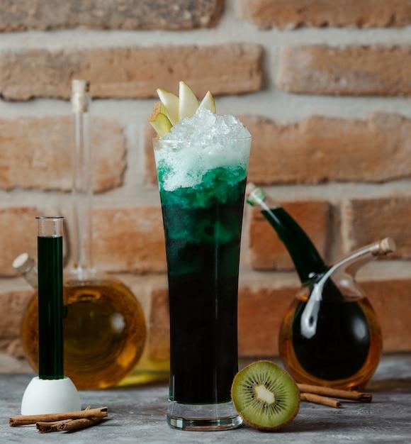 Un Verre D'alcool Vert Cocktail Avec Des Tranches De Pomme Et Des Glaçons. Photo gratuit