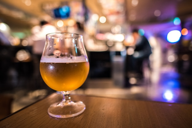 Verre de bière artisanale avec fond flou de bière pub Photo Premium