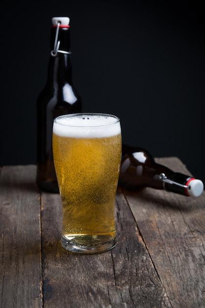 Verre de bière blonde et une bouteille Photo Premium