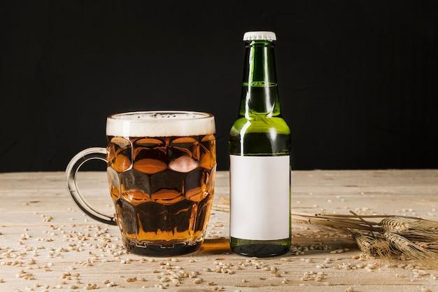 Verre de bière avec une bouteille verte et des épis de blé sur un fond en bois Photo gratuit