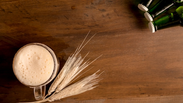 Verre, de, bière, à, épi blé, et, vert, bouteilles, sur, table bois Photo gratuit