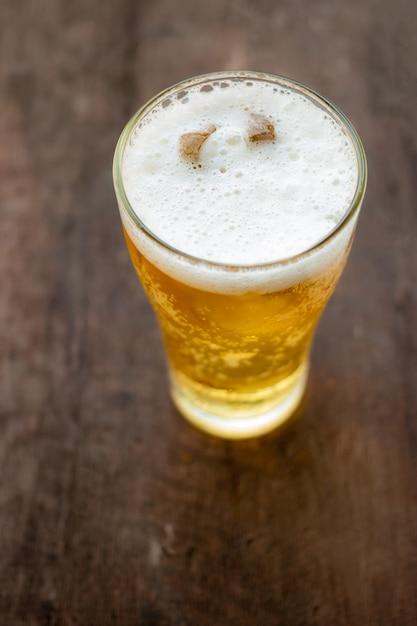 Verre de bière sur fond en bois Photo Premium