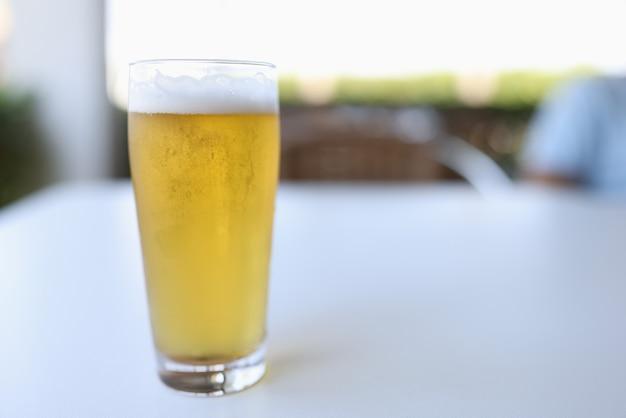 Un Verre De Bière Froide Jaune Avec De La Mousse Blanche Est Versé. Photo Premium