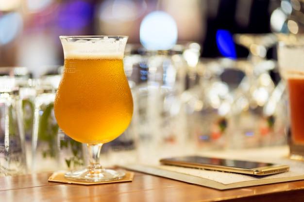 Verre de bière légère avec un téléphone intelligent sur le comptoir au club de nuit. Photo Premium