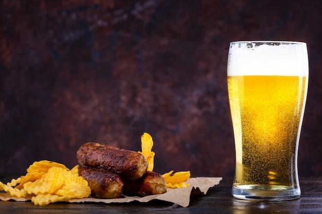 Verre de bière avec mousse, saucisses frites et chips sur fond noir Photo Premium