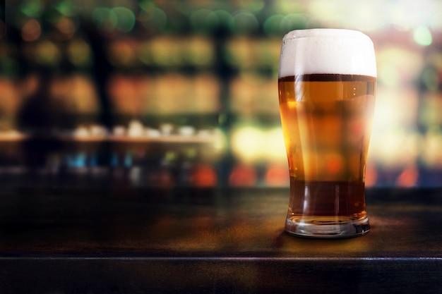 Verre de bière sur la table dans un bar ou un restaurant. vue de côté. scène de nuit Photo Premium