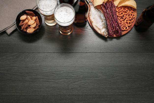 Verre à bière vue de dessus et bouteille avec plateau de nourriture avec espace de copie Photo gratuit