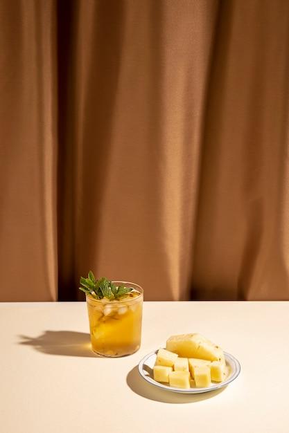 Verre de boisson cocktail avec des tranches d'ananas sur une assiette sur une table blanche contre un rideau marron Photo gratuit