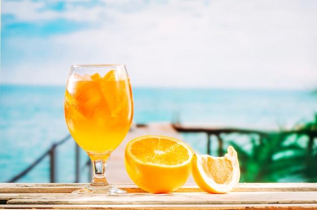Verre avec boisson orange et orange tranchée sur table en bois Photo gratuit