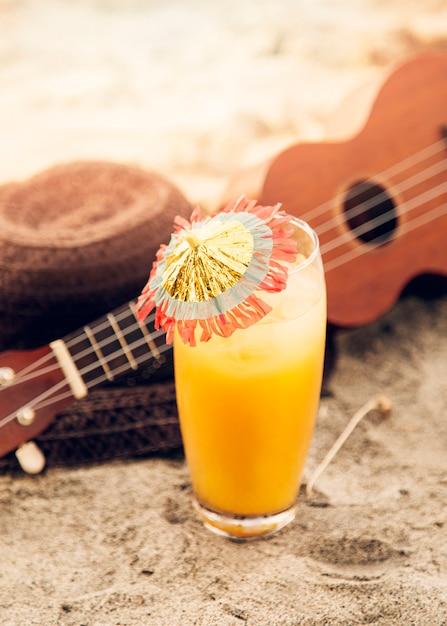 Verre avec boisson, ukulélé et chapeau de paille posé sur le sable Photo gratuit
