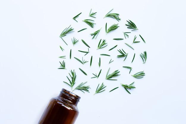 Verre bouteille médical avec des feuilles de romarin frais sur blanc Photo Premium