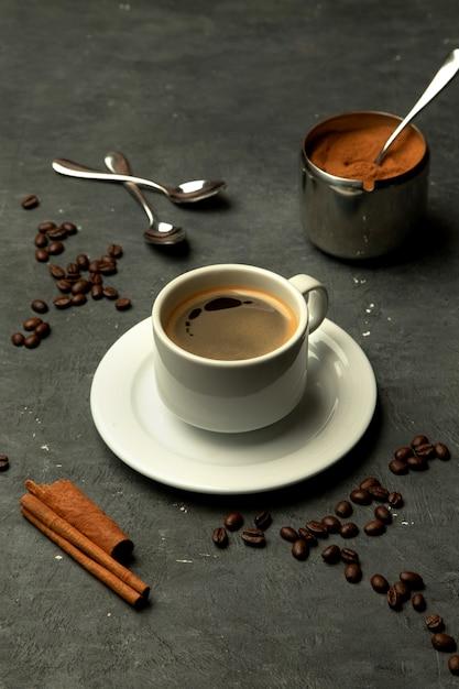 Verre de café americano sur fond gris décoré de grains de café Photo gratuit