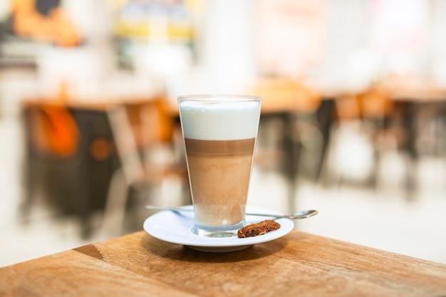 Verre à café cappuccino avec une cuillère sur une table en bois Photo gratuit