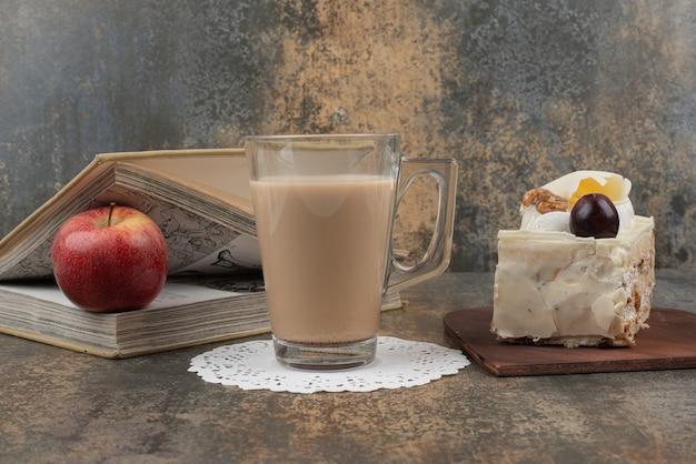 Un Verre De Café Chaud Avec Une Pomme Rouge Et Des Livres Sur Une Table En Marbre. Photo gratuit