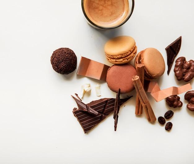 Verre à café; macarons et morceau de chocolat avec des ingrédients sur fond blanc Photo gratuit