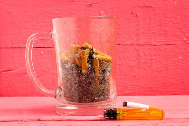 Verre cendrier à bière cigarette sur bois couleur rose Photo Premium