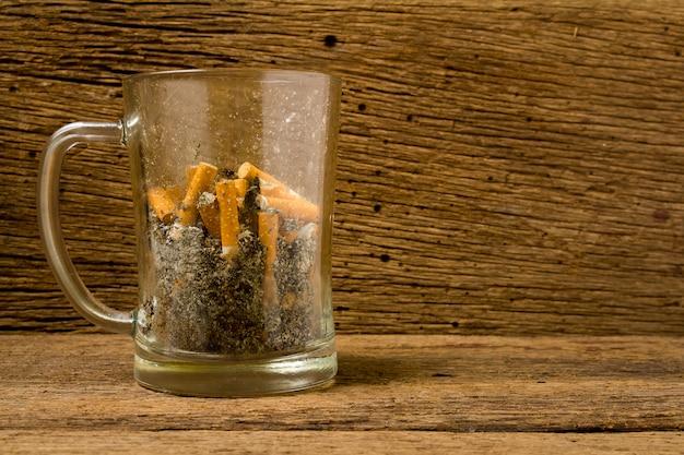 Verre cendrier à bière en cigarette sur vieux bois Photo Premium
