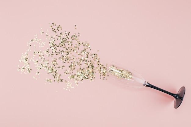 Verre de champagne versé confettis étoiles d'or Photo Premium