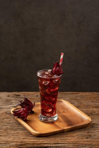 Verre clair roselle avec fruits roselle frais sur la recette de l'asie en bois table Photo Premium