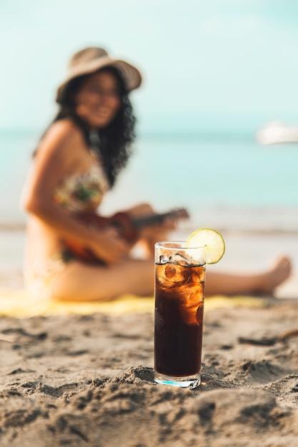 Verre De Coca Avec Glace Et Femme Sur La Plage De Sable Fin Photo gratuit