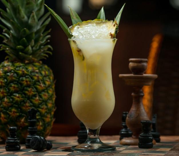 Verre à cocktail ananas glacé sur un échiquier Photo gratuit