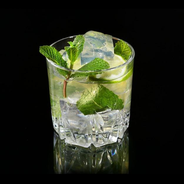 Verre de cocktail au rhum, citron vert, glaçons et feuilles de menthe sur fond de miroir noir. Photo Premium