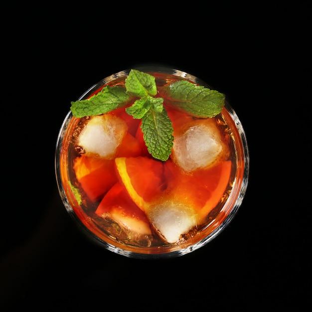 Verre de cocktail au rhum foncé avec citron vert, orange, glaçons et feuilles de menthe sur fond de miroir noir. Photo Premium