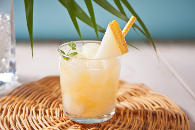 Verre à cocktail de melon sur une table blanche avec la feuille de palmier à thème tropical Photo Premium