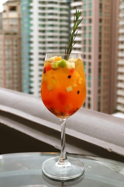Verre de cocktail de sangria avec des fruits frais sur la terrasse du bar sur le toit Photo Premium