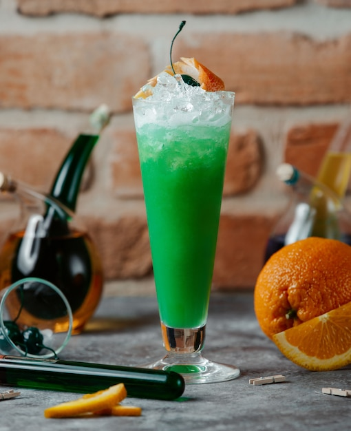 Un verre de cocktail vert avec des glaçons et des tranches d'orange. Photo gratuit