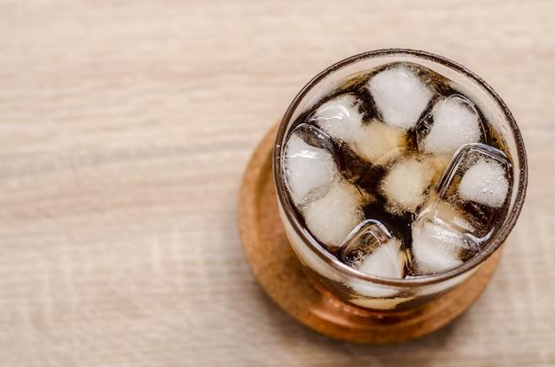 Verre de cola avec glace sur fond en bois Photo Premium