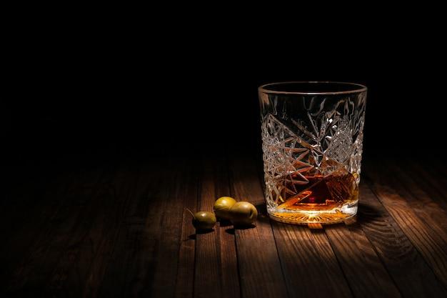 Verre en cristal avec whisky et snacks sur une table en bois sur fond noir Photo Premium