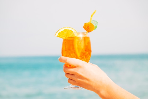Verre décoré d'une boisson orange étonnante à la main Photo gratuit