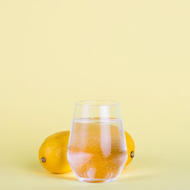 Verre à eau et citrons sur fond jaune Photo gratuit