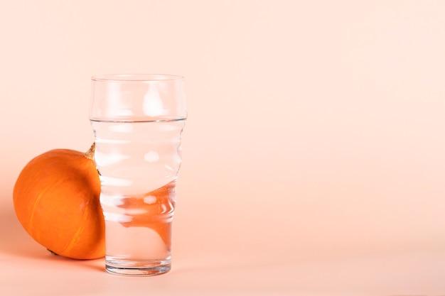 Verre à eau et citrouille avec espace de copie Photo gratuit