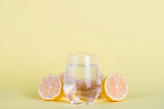 Verre d'eau entouré de citrons en tranches Photo gratuit