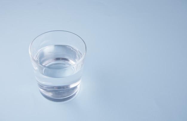 Verre avec de l'eau sur un fond bleu Photo Premium