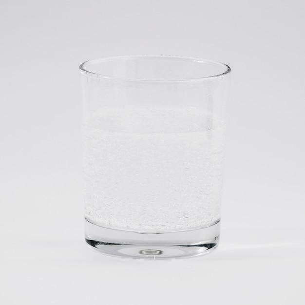 Verre d'eau sur fond gris Photo gratuit