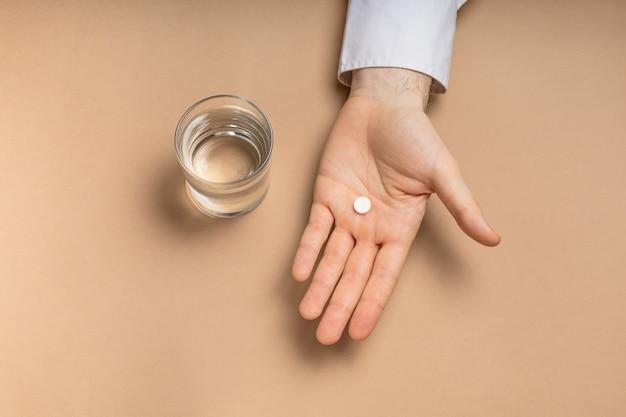 Verre D'eau Et Médicament à La Main Photo Premium